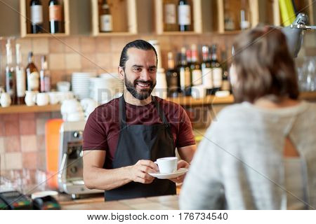 small business, people and service concept - happy man or waiter giving cup with hot drink to customer at coffee shop or bar