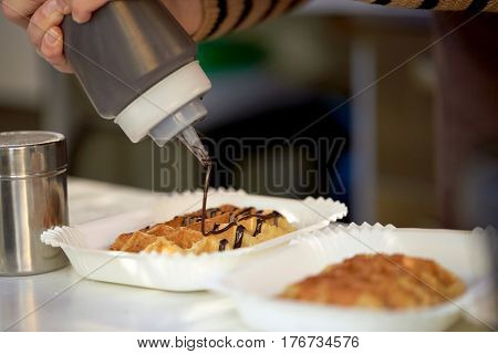 food, cooking, dessert and people concept - close up of cook adding chocolate syrop to waffle