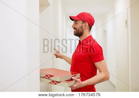 food delivery, mail and people concept - man delivering pizza in paper boxes to customer home and ringing doorbell