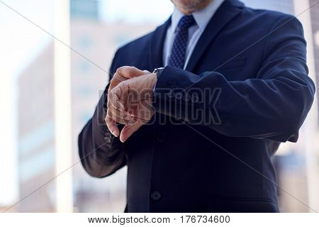business and people concept - senior businessman checking time on his wristwatch in city
