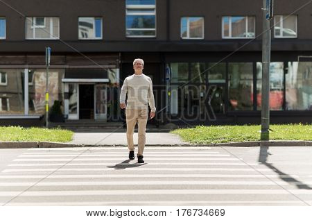 leisure and people concept - senior man walking along summer city crosswalk