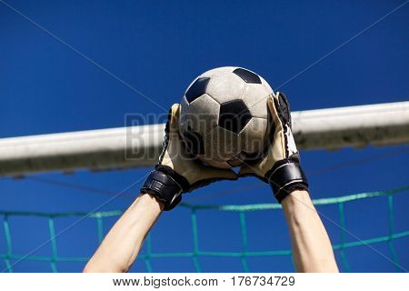sport and people - soccer player or goalkeeper hands catching ball at football goal over blue sky