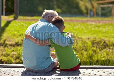 family, generation, relations and people concept - happy grandfather and grandson hugging on berth