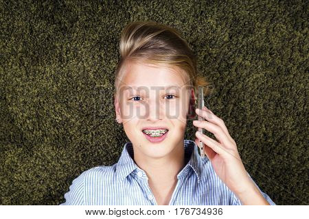 Teen with phone in hands. Conversation on the smartphone modern communications.Orthodontics and bite correction.