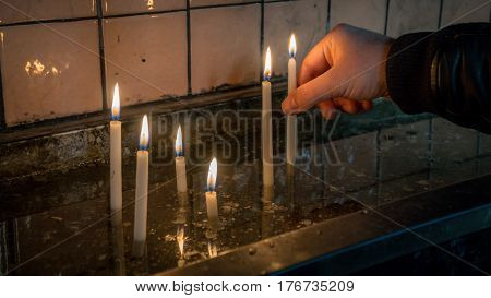 Istanbul, Turkey - February 18, 2017: Man making a wish with sacred burning candles in church in Saint Antoine church in Taksim