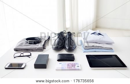 business, style and objects concept - formal male clothes, gadgets and personal stuff on table at home