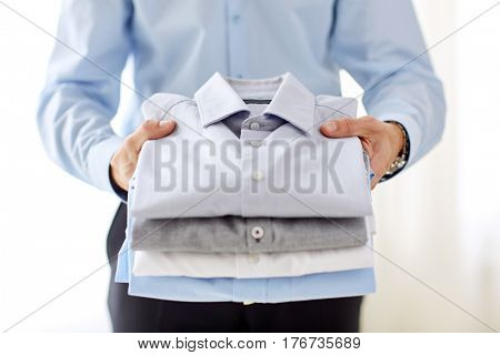 business, clothes, formal wear and people concept - close up of businessman holding shirts