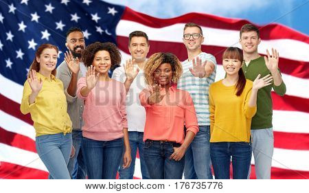 diversity, race, ethnicity and people concept - international group of happy smiling men and women waving hand over american flag background