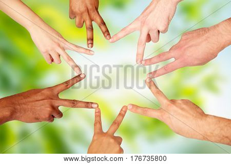 diversity, race, ethnicity, international and people concept - group of hands showing peace hand sign over green natural background