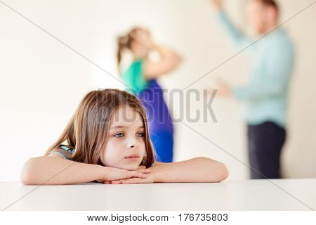 childhood, social issue, sadness and people concept - beautiful sad girl and parents arguing at home