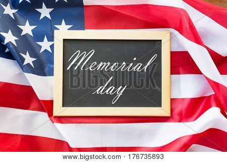 patriotism and national holidays concept - memorial day words on chalkboard and american flag
