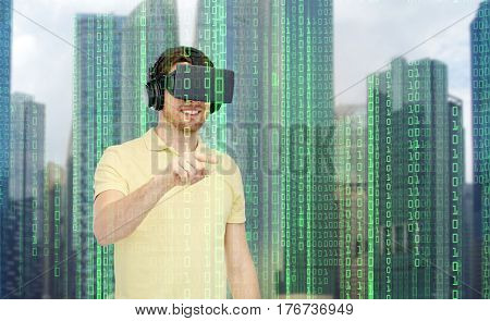 modern technology, cyberspace, entertainment and people concept - happy young man with virtual reality headset or 3d glasses playing game over city skyscrapers and binary code background