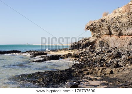 Black rocks of Costa Calma beach. Blue sea line. Playa Barca, Fuerteventura, Canary islands, Spain. Istmo de la pared view