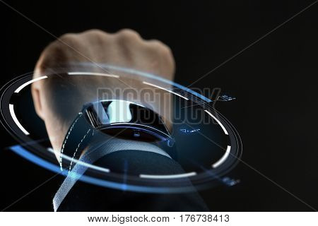 business, people and technology concept - close up of businessman hand with smartwatch and virtual projection over black background