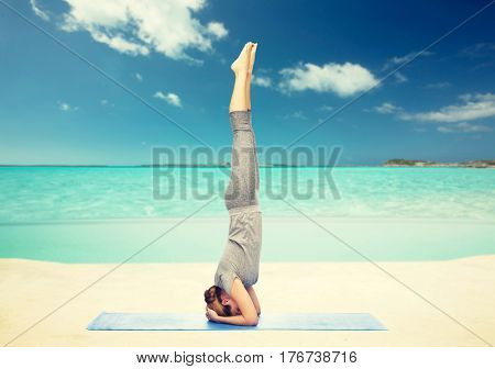 fitness, sport, people and healthy lifestyle concept - woman making yoga in headstand pose on mat over sea and sky background