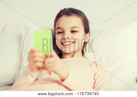 people, children, rest and technology concept - happy smiling girl lying awake with smartphone in bed at home