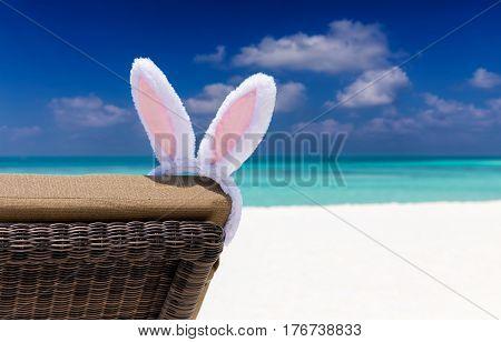 Easter bunny ears on sun chair at a tropical beach setting