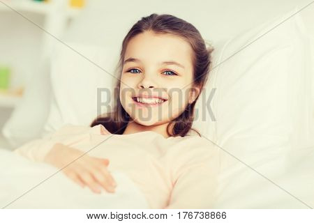 people, children, rest and comfort concept - happy smiling girl lying awake in bed at home