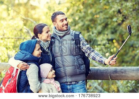 travel, tourism, hike, technology and people concept - happy family with backpacks taking picture by smartphone and selfie stick in woods