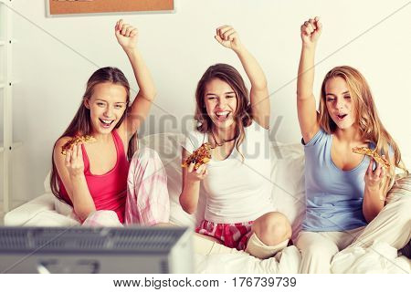 friendship, people, pajama party, entertainment and junk food concept - happy friends or teenage girls eating pizza and watching tv at home