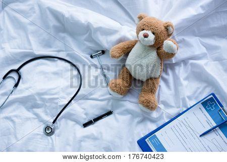 Stethoscope reflex hammer and clipboard with medical document lying on bed near teddy bear