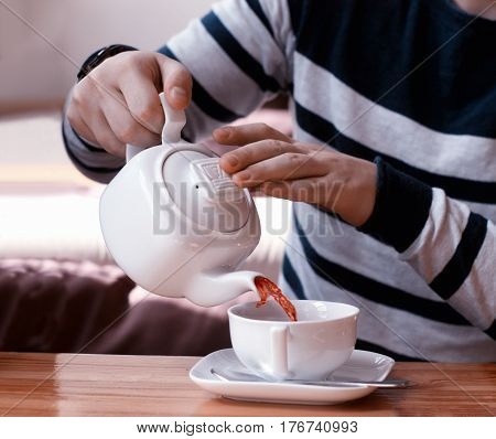 man pours fruit tea from teapot into the white cup on wood table