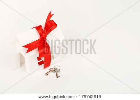 white cardboard house with ribbon and keys on white surface