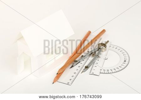 white cardboard house with pencils rulers and compasses on white