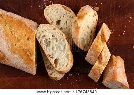 Bread in slices on a dark brown board
