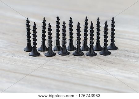 Black wood screw on a wooden background. Side view