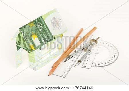 house wrapped in euro banknotes with pencils rulers and compasses on white