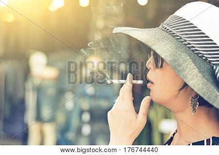 woman smoking at the market at street