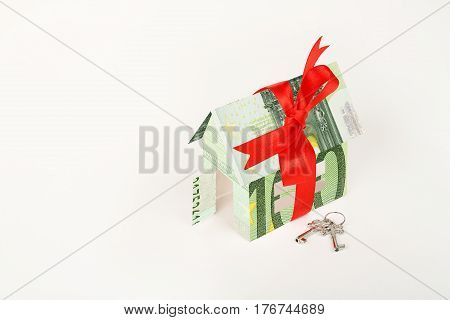 house wrapped in euro banknote with ribbon and keys on white surface