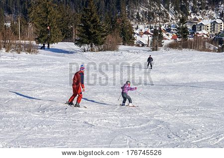 Slavsko, Ukraine - January 30, 2017: Little boy with his father skiing on a mountain slope in Carpathians