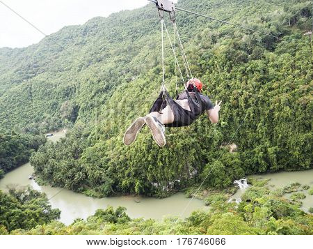 Young man has a sky experience with Zip Line and extreme sport in Philippine