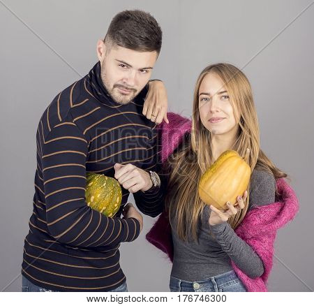 Whiskered and bearded Man in striped jacket with pretty girl in pink sweater holding pumpkins in hands on grey backgrou