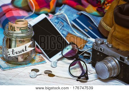 wanderlust. adventure concept. background - what to take for a trip - camera smartphone jar with money glasses shoes jeans accessories