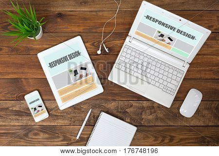 Working Place of web Designer on wood Table with responsive Site Theme on Laptop Tablet and Telephone Screens and blank Page of Paper Notepad Top View flat Lay.