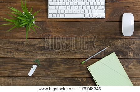 Cozy mix of Vintage and Technology Business Theme on wood Table with green Pencil Flower Computer Keyboard paper Notepad and compact flash drive. Blank Page of Notepad for copy the text