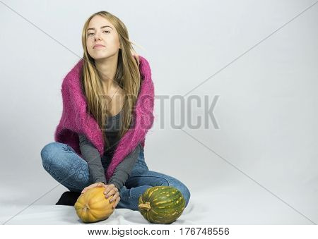 Girl sitting Legs crossed beside basket with fruits pumpkins on grey background holding apple in hand