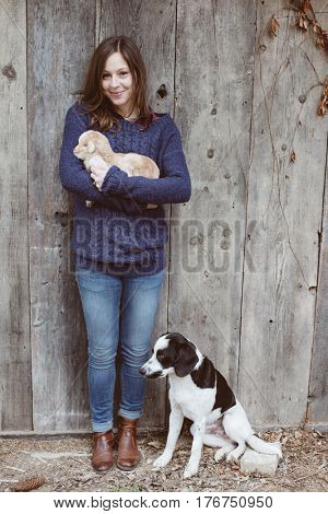 Young adult woman with baby goat and young dog at farm