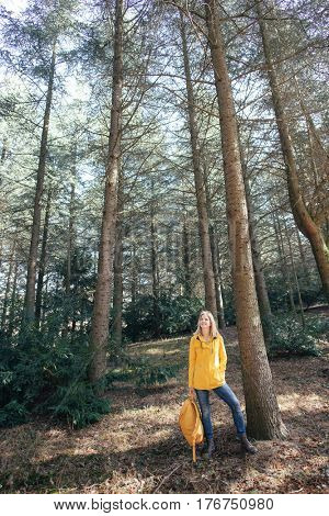 Carefree woman standing in forest, arms outstretched