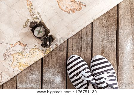Top View Of Compass, World Map And Striped Shoes On Wooden Table, Traveling Concept