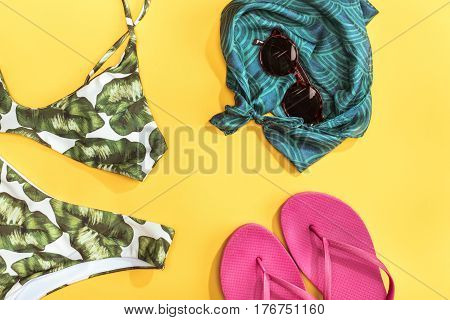 top view of swimsuit shawl sunglasses and flip flops. Summer holidays concept