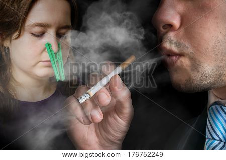 Passive smoking concept. Selfish man is smoking a cigarette. Woman cant breathe and has peg on her nose.
