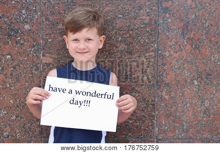 Have a wonderful day. a todler cute smiling and holding a poster with an inscription Have a wonderful day.a small boy wishes a good day.