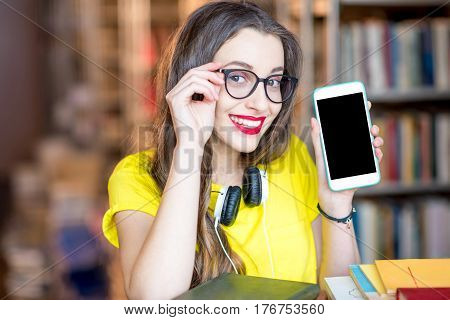 Young smiling student showing smart phone with empty screen standing at the library. Mobile application concept