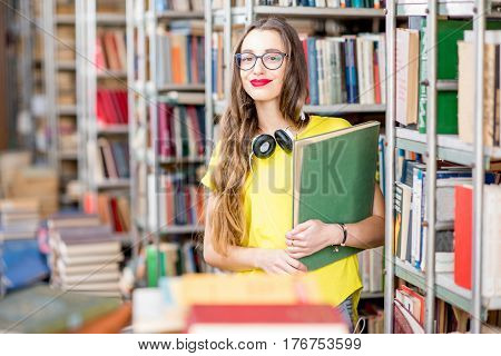 Young happy and enthusiastic female student reading books at the old library