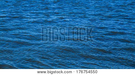 Blue water surface background. Ripples on the water of river. Water background. Water surface texture.