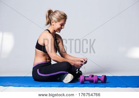 Beautiful Female Fitness Model Resting After A Hard Training Session And Taking A Selfie For Social
